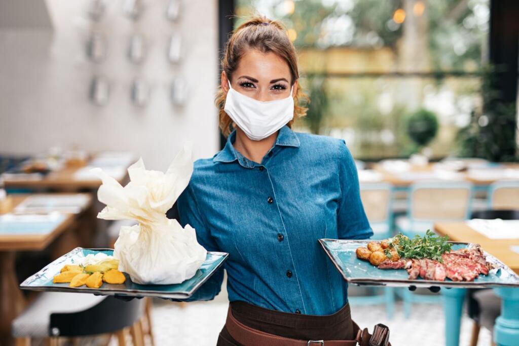 Una cameriera con mascherina
