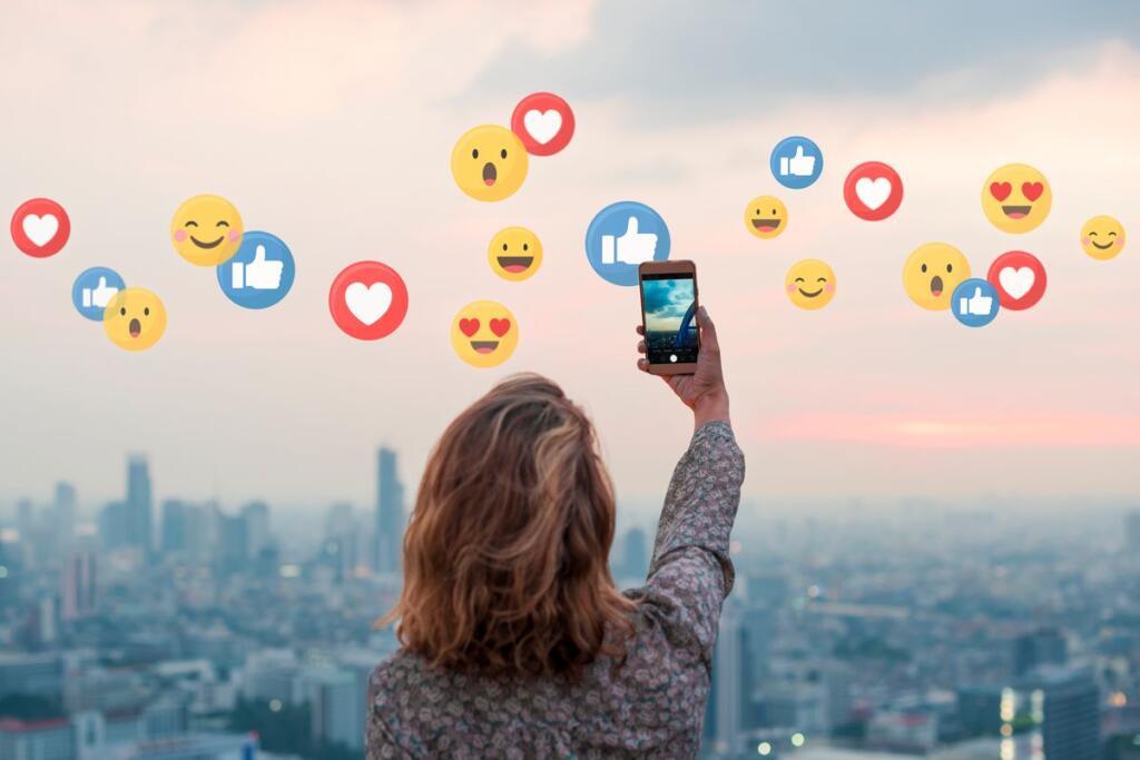 Ragazza con smartphone da cui escono reaction ed emoticon