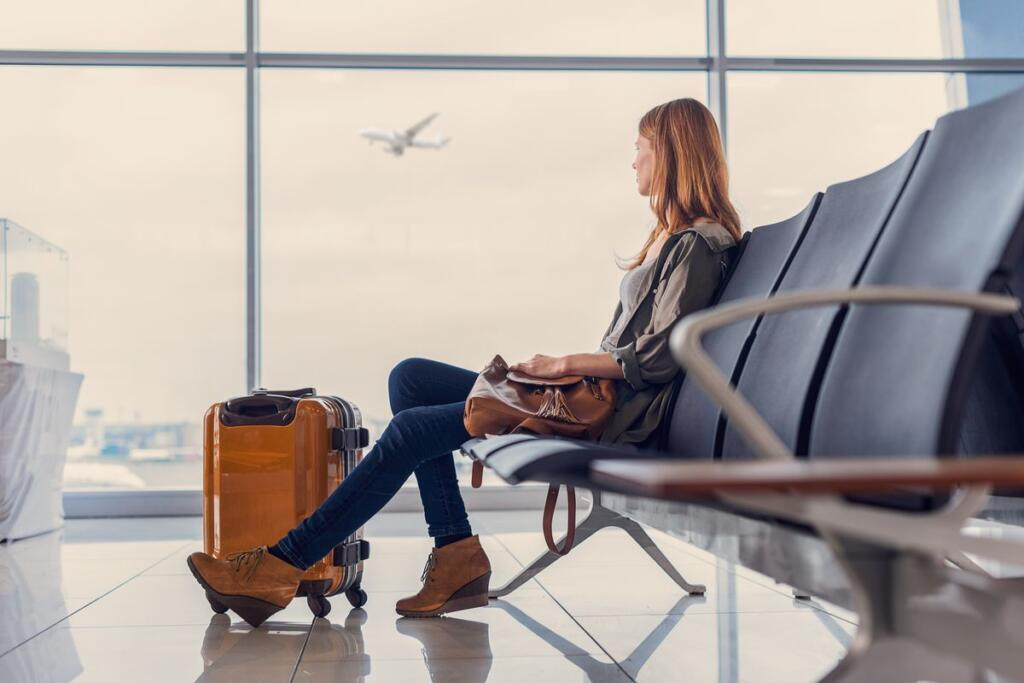 Una donna attende il volo in aeroporto