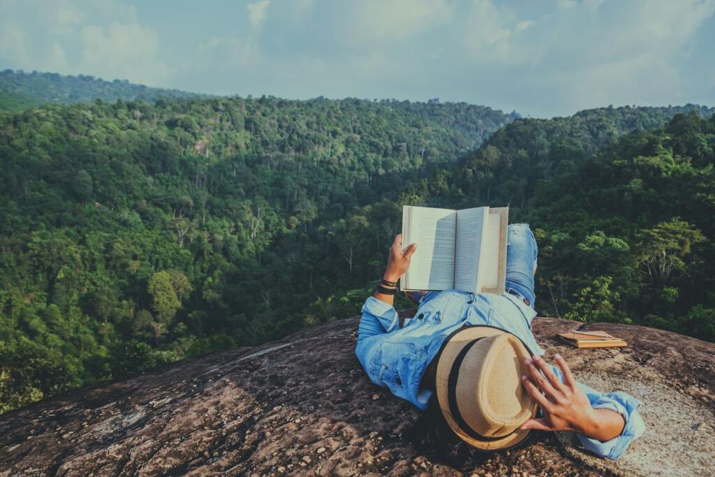 Uomo legge un libro in montagna