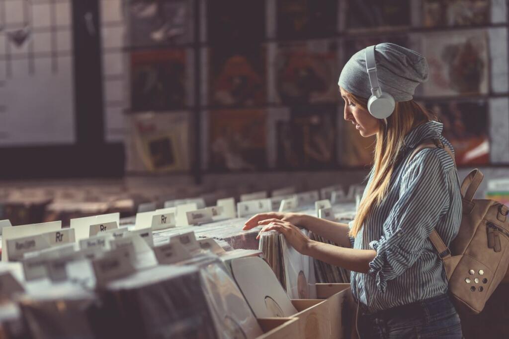 Una donna con le cuffie in un negozio di vinili